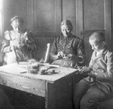 Mutter mit Kindern bei der Herstellung von Bürsten, zwischen 1890 und 1910