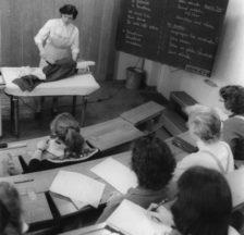 Haushaltungsschule: eine Lehrerin doziert vor angehenden Hausbeamtinnen über die richtige Hosenpflege (1957)