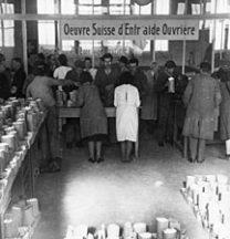 Verteilung von Colis Suisse 1944 in Lyon: Jeder Arbeiter erhält 2 kg Zucker, 1 kg Linsen, 1/2 kg Teigwaren, 1 Büchse Tomatenpüree und 2 Büchsen Sardinen. (F_5025-Fb-006)